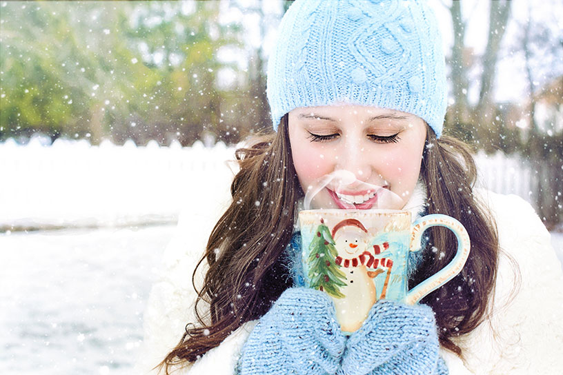 woman drinking hot chocolate in finland out in snow