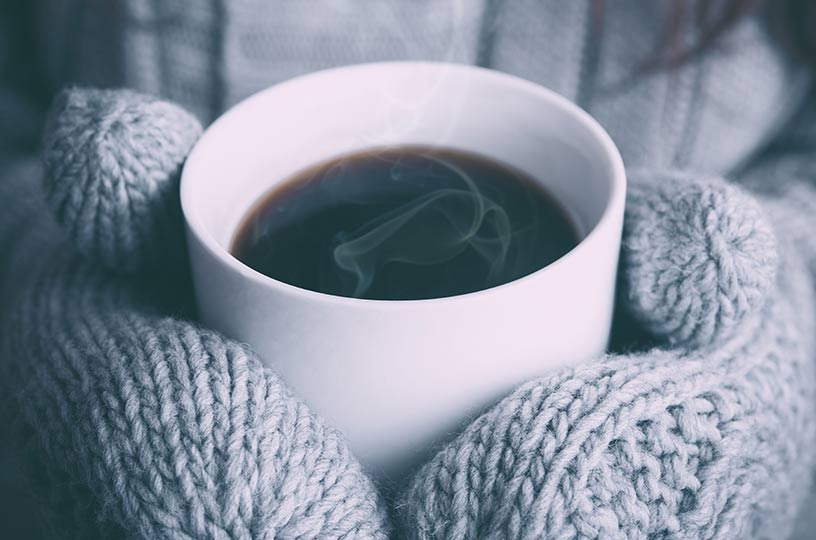 warm cup of coffee with gloves