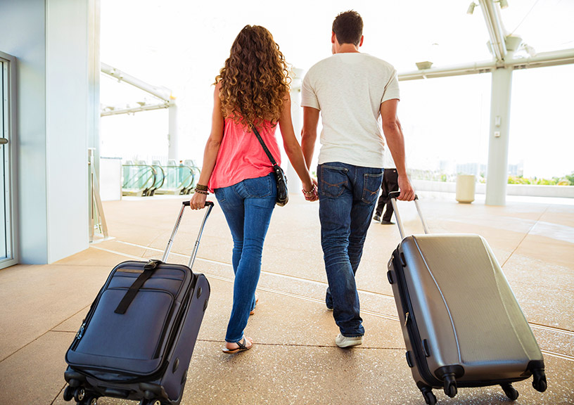 couple walking out of airport with luggage