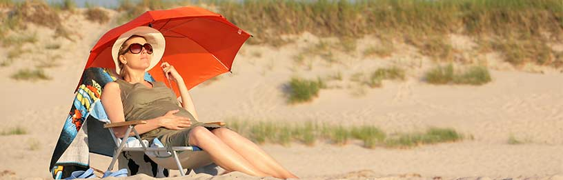 Pregnant woman on beach with umbrella
