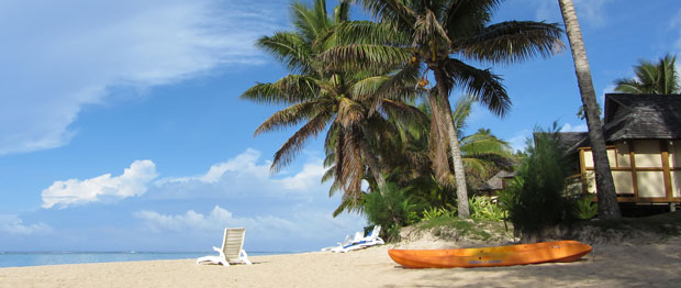 A lone beach chair and palm trees at Palm Grove's Beach, Vaimaaga, Rarotonga, Cook Islands