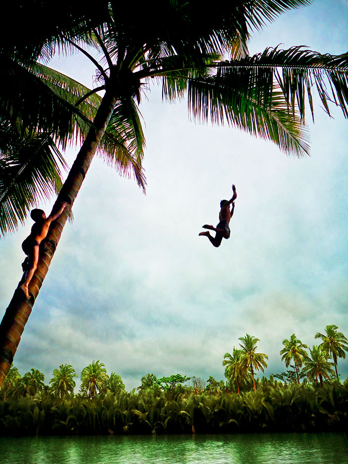 Cover-More New Zealand Facebook photo competition winner: Children jumping off coconut tree into water in the Philippines