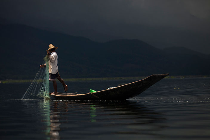 Cover-More New Zealand Facebook photo competition winner: Fisherman rowing out his net on Inle Lake after a rain shower