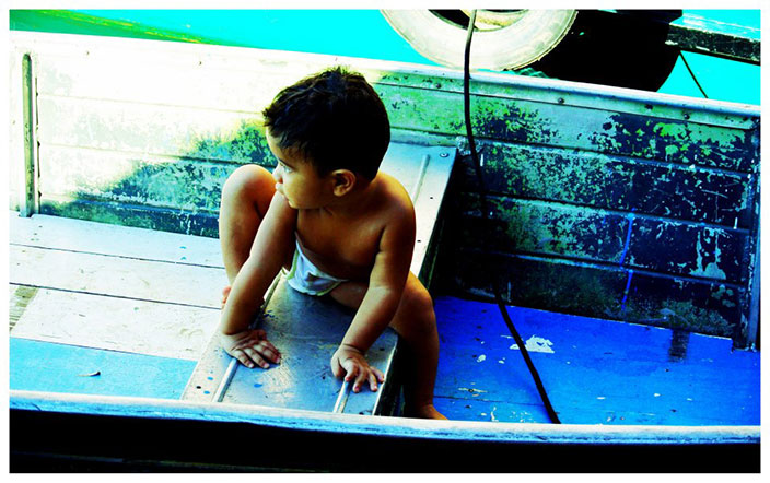 Cover-More New Zealand Facebook photo competition winner: A toddler climbing in a boat in the Amazon Jungle in Brazil