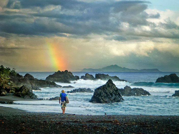 Cover-More New Zealand Facebook photo competition winner: Surfer walks towards the beach as a rainbow appears above him