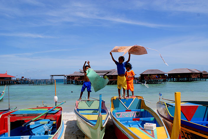 Cover-More New Zealand Facebook photo competition winner: Children playing on colourful boats on a Malaysian beach