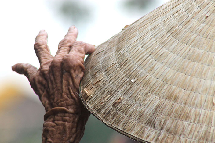 Cover-More New Zealand Facebook photo competition winner: Old woman adjusting her woven hat at a river bank in Vietnam