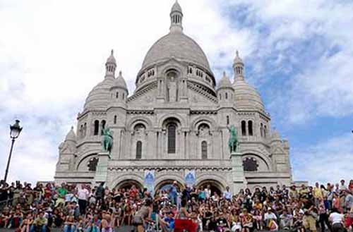 Crowds gather on the steps of Sacre Coeur to look over the landscape of Paris from the highest point in the city.
