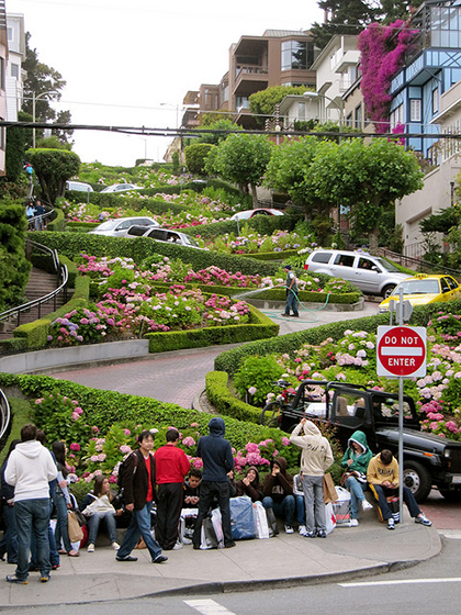 At the bottom of Lombard Street's zig-zag pattern with a number of cars navigating the sharp turns.