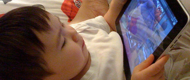 A child lays down and watches a video on an iPad