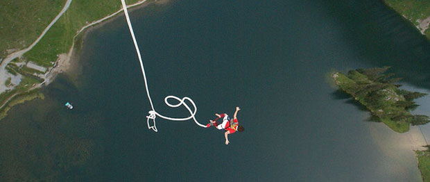 Man bungee jumps over water