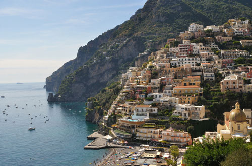 A view of Positano, a stunningly beautiful Italian city that's carved into the hills of the Amalfi Coast. Positano falls alone one of the routes of the best road trips in the world.